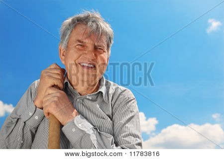 Old Senior In Striped Shirt With Shove Smiling And Looking At Camera, Blue Sky With Clouds