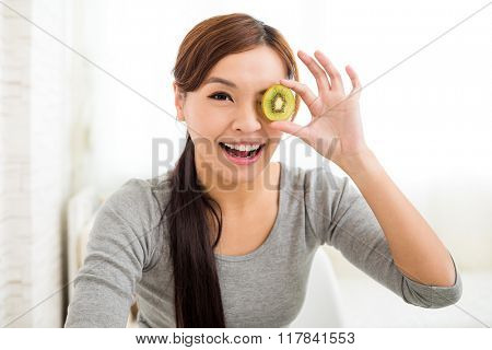Young woman showing slices of kiwi fruit