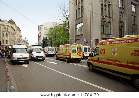 Many Yellow And White Emergency Ambulances On Street And Old Buildings