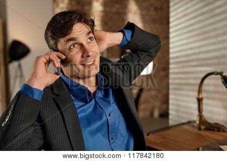Businessman talking on mobile, hand behind ears, looking up.