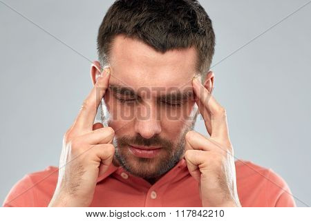 people, crisis, emotions and stress concept - man suffering from head ache or thinking over gray background