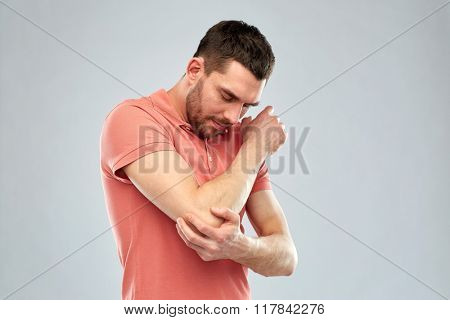 people, healthcare and problem concept - unhappy man suffering from pain in hand over gray background