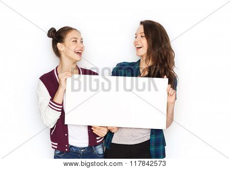 people, friends, teens and friendship concept - happy smiling pretty teenage girls holding and showing white blank board