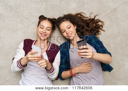 people, friends, teens and friendship concept - happy smiling pretty teenage girls lying on floor with smartphones