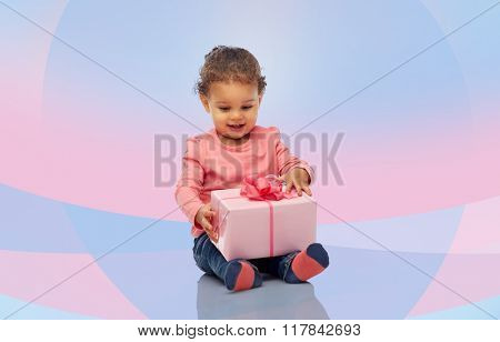 childhood, fashion, birthday, holidays and people concept - happy smiling little african american baby girl with gift box sitting on floor over pink violet background