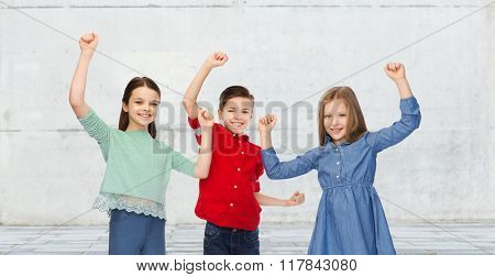 childhood, friendship, success, gesture and people concept - happy smiling boy and girls raising fists and celebrating victory over urban street background