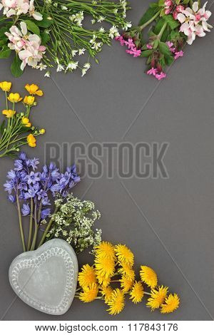 Spring wild flower abstract border with heart shaped stone over grey background.