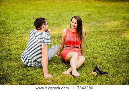 Young couple talking on grass