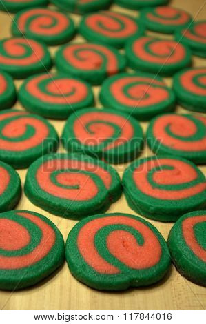 batch of delicious homemade red and green holiday butter sugar cookies on wood