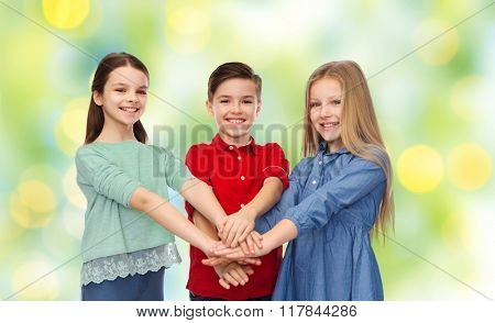 childhood, friendship, summer holidays, friendship and people concept - happy smiling children with hands on top over green lights background
