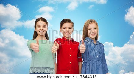 childhood, friendship, gesture and people concept - happy smiling children showing thumbs up over blue sky and clouds background