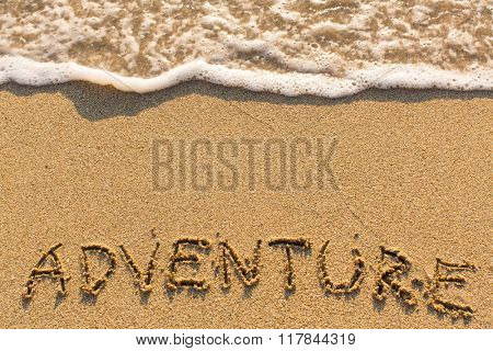 Adventure - inscription on sand beach with the soft wave.