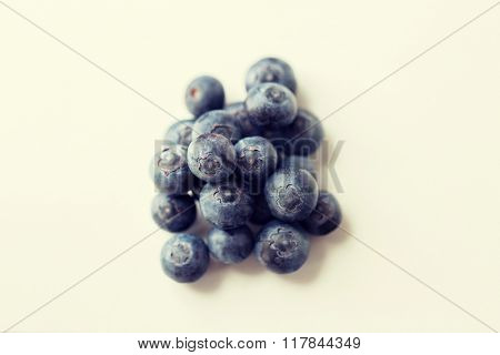 fruits, berries, diet, eco food and objects concept - juicy fresh ripe blueberries on white