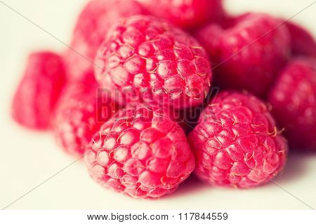 fruits, berries, diet, eco food and objects concept - juicy fresh ripe red raspberries on white