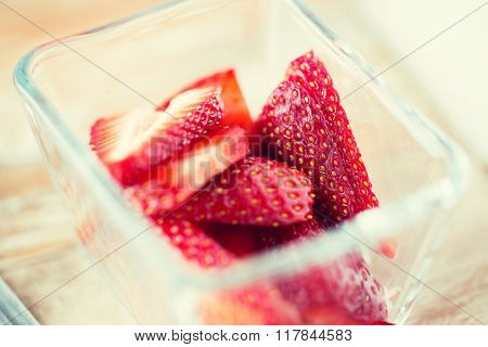 fruits, berries, diet, eco food and objects concept - juicy fresh ripe red strawberries in glass bowl