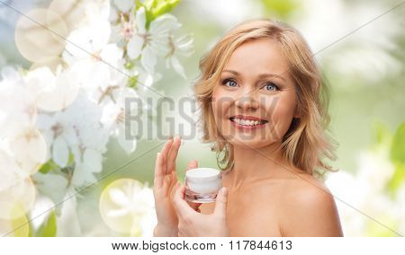 beauty, people, skincare and natural cosmetics concept - happy woman applying cream to her face over cherry blossom background