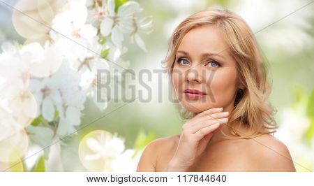 beauty, people, skincare and natural cosmetics concept - woman with bare shoulders touching face over cherry blossom background