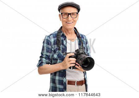 Studio shot of a senior photographer holding a black camera isolated on white background