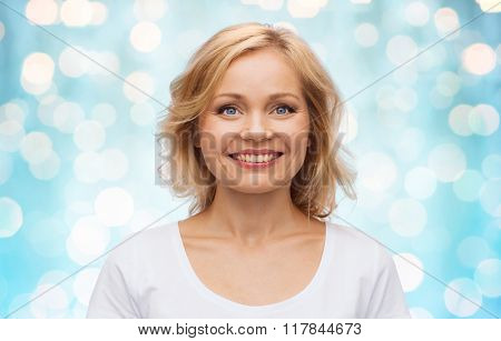 happiness and people concept - smiling woman in blank white t-shirt over blue holidays lights background