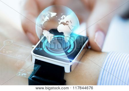 business, technology, communication, connection and people concept - close up of woman hands globe hologram on smartwatch