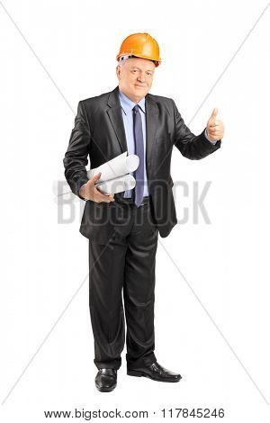 Full length portrait of a mature architect holding construction plants and giving thumb up isolated on white background