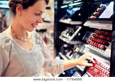 Beautiful Young Woman Chooses Lipstick In Store. Bid Assortiment