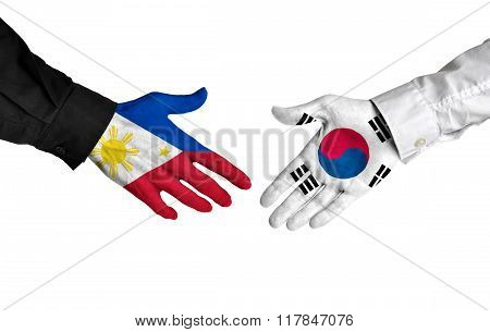 Philippines and South Korea leaders shaking hands on a deal agreement
