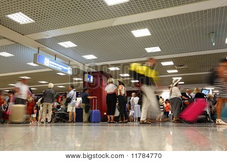 People Waiting Board To Airplane In Hall Of Airport. People Move With Luggage