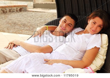Young Husband And Wife In White Dress Sitting On Black Wicker Chair And Hug