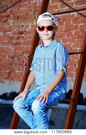 Cool modern eight-year boy posing on the city street by the brick wall. Kid's fashion.