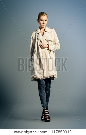 Fashion shot of a female model posing at studio in a coat. Beauty, fashion. Full length portrait.