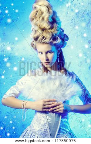 Portrait of a beautiful young lady in a luxurious historical dress and high hairdo. Baroque and Renaissance style. Elegant Ice Queen over frozen background.