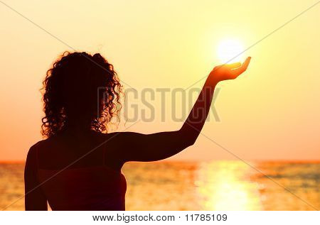 Bella joven de pie en la playa, puesta de sol, con el sol en mano