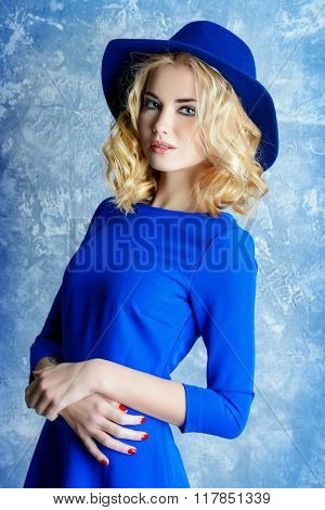 Fashion portrait of a beautiful blonde girl wearing blue dress and elegant hat.