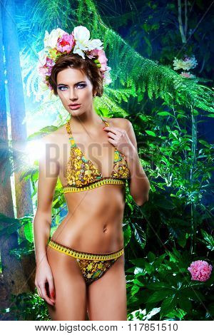 Beautiful slender woman in bikini among tropical plants. Beauty, fashion. Spa, healthcare. Tropical vacation.