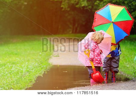 little boy and girl with umbrellas playing in water puddle