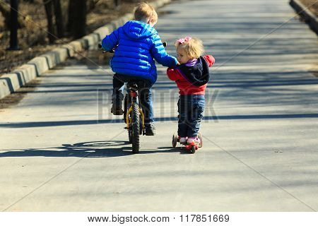 little boy on bike teaching baby girl to ride scooter