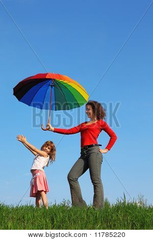 Mother stands  and holding colorful umbrella over her daughter