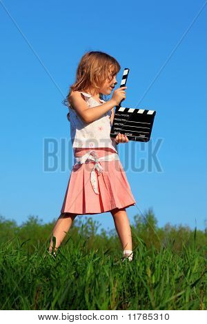 Girl stands in field with green grass with clapperboard in hands