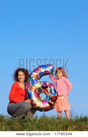 Mother and daughter holding an inflatable figure of six
