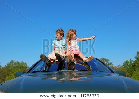Little Boy And Girl Sitting On Car Roof On Blue Sky, Looking To Sides And Showing By Finger