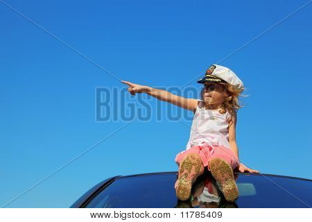 Little Girl Sitting On Car Roof Showing By Finger On Left Side, Blue Sky