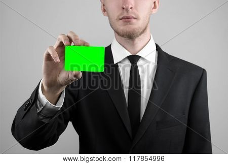 Businessman In A Black Suit And Black Tie Holding A Card, A Hand Holding A Card, Green Card, Card Is