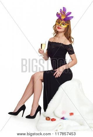 Young woman in black evening gown and a glass of champagne.  Carnival mask on face. Sit on white fur. Holiday and party concept.