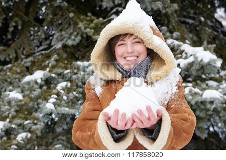 Woman portrait at winter season with snow on head and in her hands