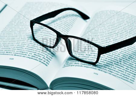 closeup of a pair of black plastic-rimmed eyeglasses on an open book, in duotone