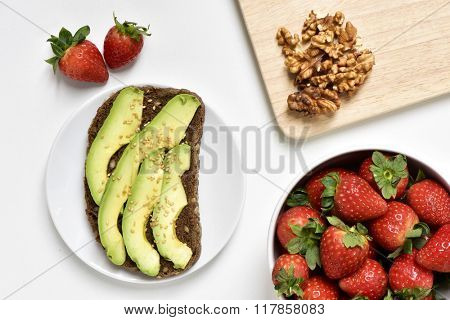 high-angle shot of an avocado toast in a white plate, a white bowl full of strawberries and some peeled walnuts on a wooden chopping board, on a white surface