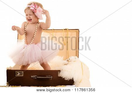 little girl sings while standing in a suitcase