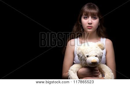 Scared blond teenage girl with teddy bear