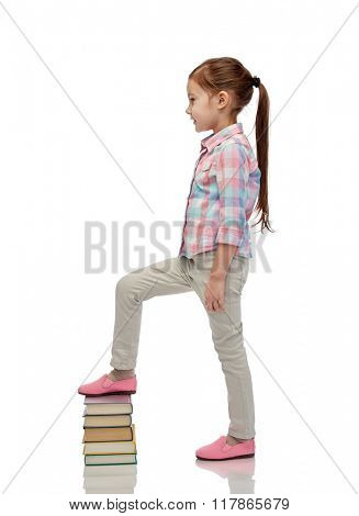 childhood, school, education and people concept - happy little girl stepping on book pile